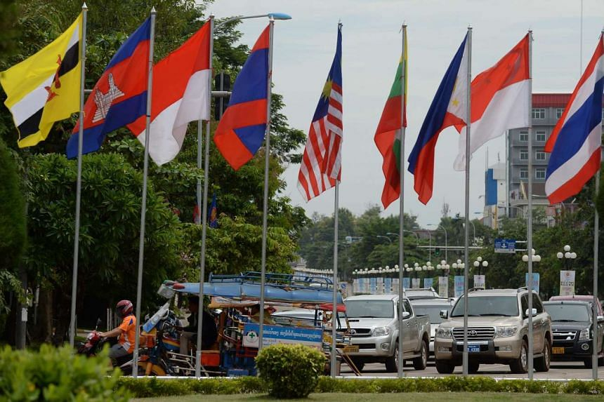 Cars and tuk-tuks move past a row of Asean member countries' flags in Vientiane, the capital of Laos, on July 23, 2016.