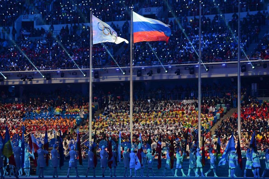 This file photo taken in 2014 shows an Olympic Games flag and a Russian flag waving during the closing ceremony of the Winter Olympics in Sotchi. Russia operated a state-dictated doping system during the 2014 Sochi Winter Olympics and other events.