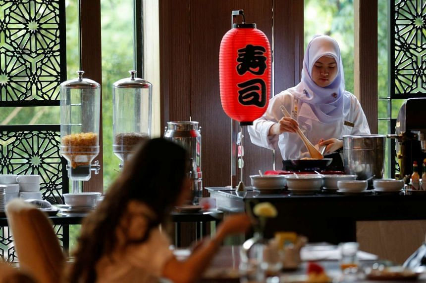 A Muslim employee preparing food for guests during breakfast at the Al Meroz hotel, on Aug 29, 2016.