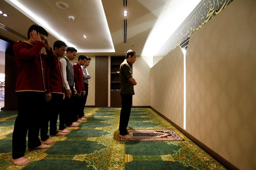Muslim employees praying inside one of the prayer rooms at the Al Meroz hotel in Bangkok.