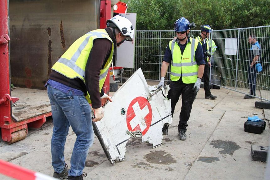 Employees help to clean up the crash site where a Swiss fighter jet crashed in Bitgum on June 9. A Swiss fighter crashed and burst into flames in the Netherlands after hitting another jet during a training session before an air show, officials said.