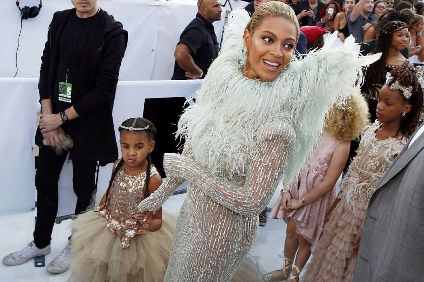 Singer Beyonce, on the red carpet with her daughter Blue Ivy, wore a slinky nude gown by Francesco Scognamiglio with feathered wings.
