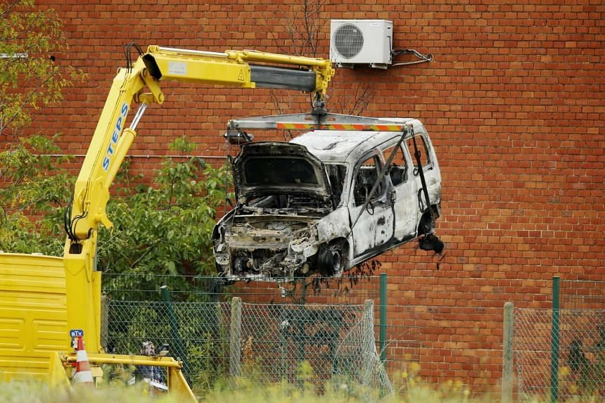 A burned-out car being lifted yesterday at the National Institute for Criminalistics and Criminology. Attackers rammed a car through the gates of the facility in Brussels and then started a fire. Part of the building was damaged in the fire.
