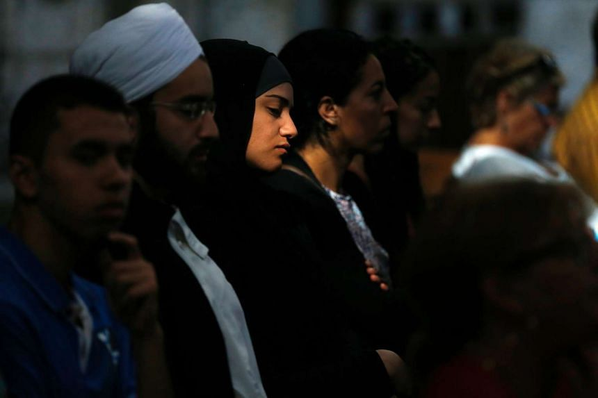 A Muslim woman looks on as people attend a Mass in tribute to slain priest Jacques Hamel in the Rouen Cathedral on July 31. Religious tension have been high in France in the wake of Islamic militant attacks, as well as a recent ban on burkinis on Fre