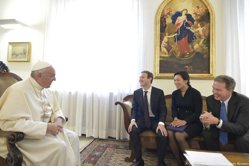 A handout picture released by the Vatican newspaper L'Osservatore Romano shows Pope Francis (left) meeting with the founder and CEO of Facebook, Mark Zuckerberg (second from left) and his wife Priscilla Chan (second from right), during a private audi