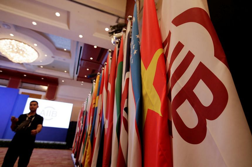 Flags of the Asian Infrastructure Investment Bank (AIIB) (right) and member states are set up for the opening ceremony of the first annual meeting of AIIB in Beijing on June 25, 2016.