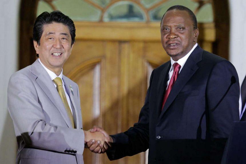 Japanese Prime Minister Shinzo Abe (left) shakes hands with Kenyan President Uhuru Kenyatta during a joint news conference at the State House in Nairobi, Kenya on Aug 28, 2016.