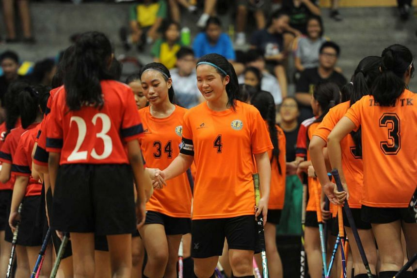 Tanjong Katong Secondary School girls (in orange) shaking hands with the team from St Margaret's after they won the National Girls C Division floorball championship, on Aug 31, 2016.