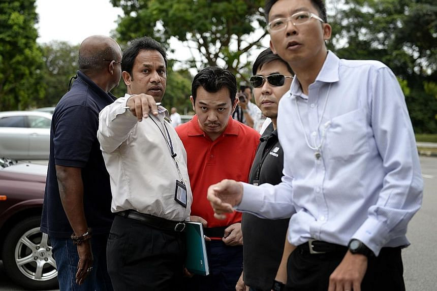 Investigators taking Lee (in red) back to Sembawang Park in 2014, where he led them to the bag which contained the ransom money. He had thrown it into the bushes.