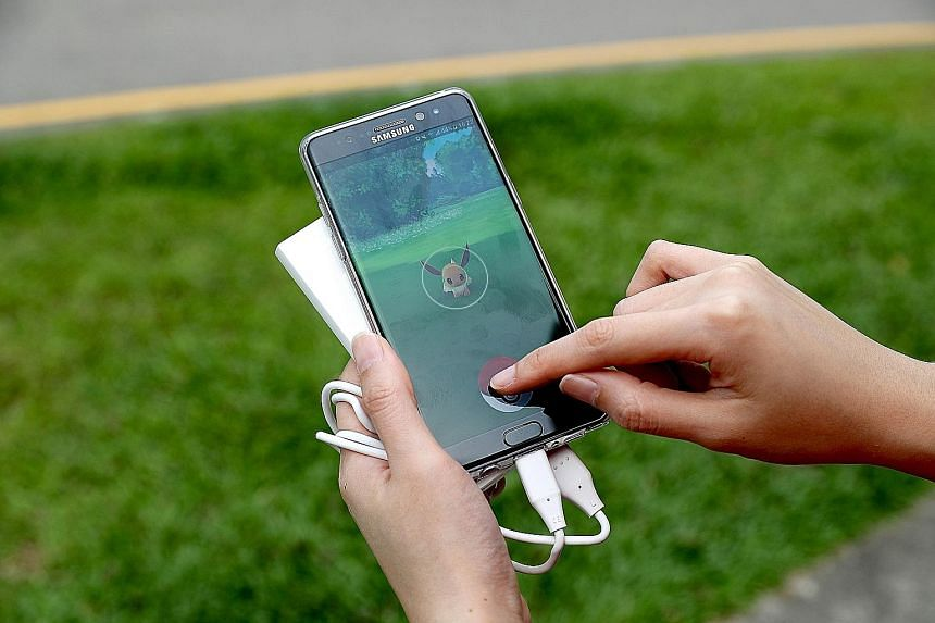 A Pokemon Go trainer playing the game while having her smartphone hooked to a power bank.