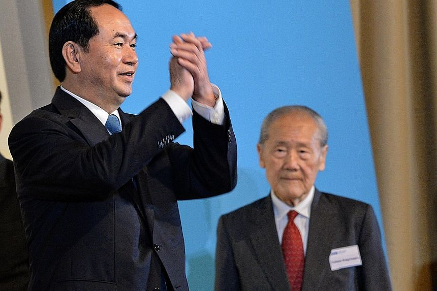 Vietnamese President Tran Dai Quang (left) greeting the audience at the 38th Singapore Lecture yesterday, where he delivered his talk before 550 people, including political and business leaders. On the right is Professor Wang Gungwu, chairman of the