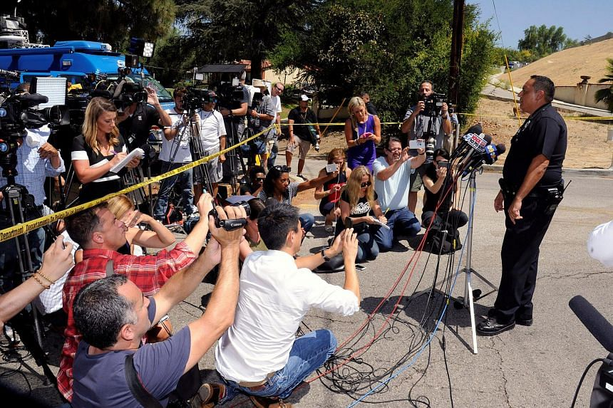 Los Angeles Police Department representative briefs the media as they wait outside the home of singer Chris Brown following an early morning 911 call from a woman there who asked for help in the Tarzana neighborhood of Los Angeles, California, US on