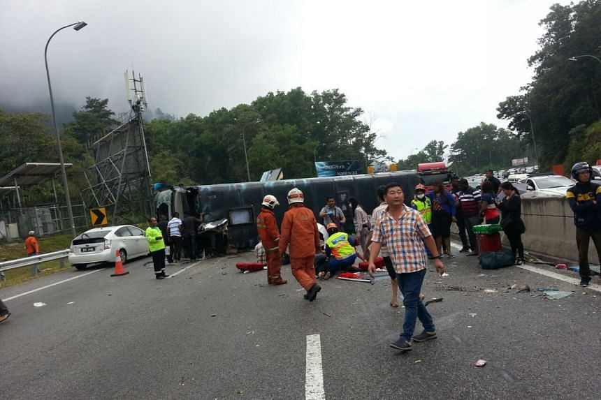 Rescue officers tend to the injured after a tour bus overturned on the Karak-KL highway while returning from Genting Highlands, on Aug 31, 2016.