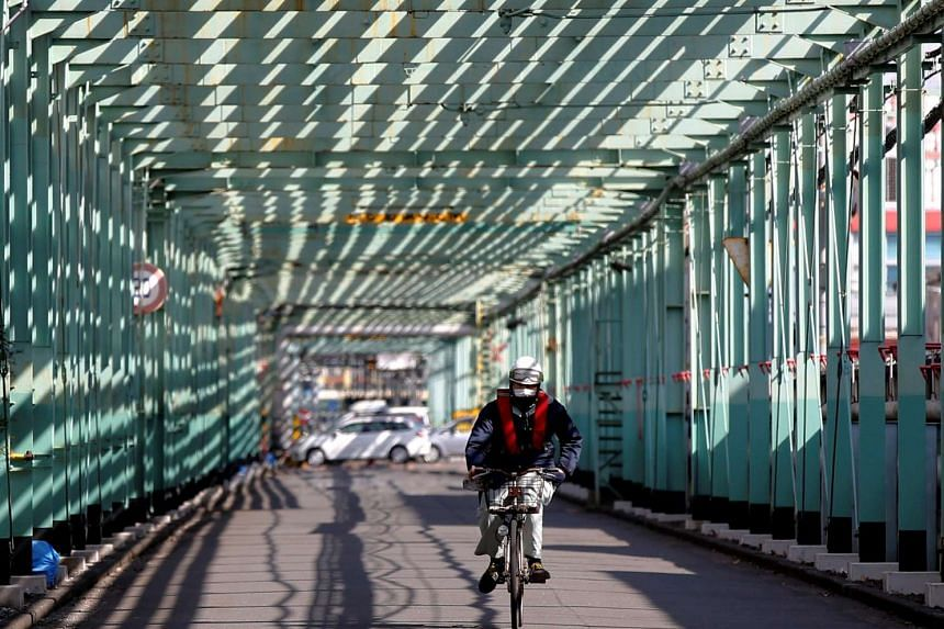 A worker cycles in a factory at the Keihin industrial zone in Kawasaki, Japan on Feb 17, 2016.