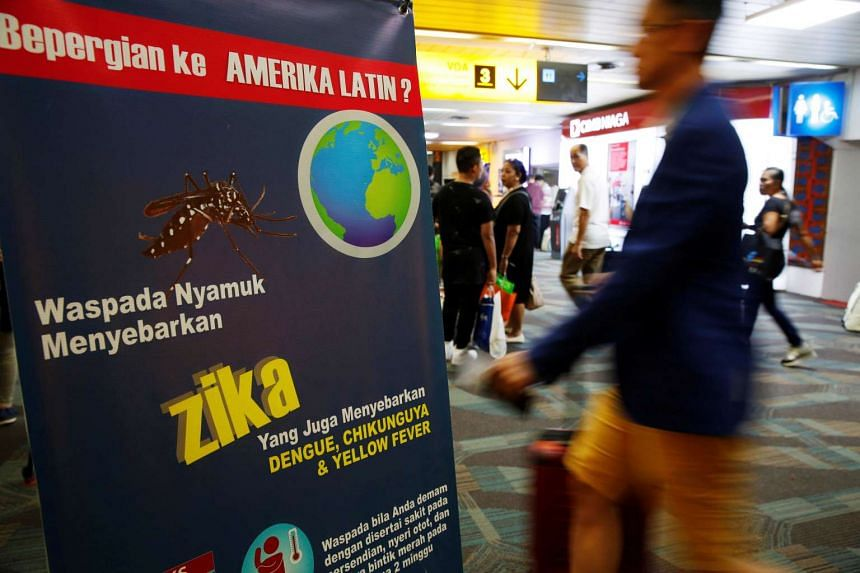 Passengers arriving from Singapore walk near a banner about Zika virus at the Soekarno-Hatta airport in Jakarta on Aug 30, 2016.