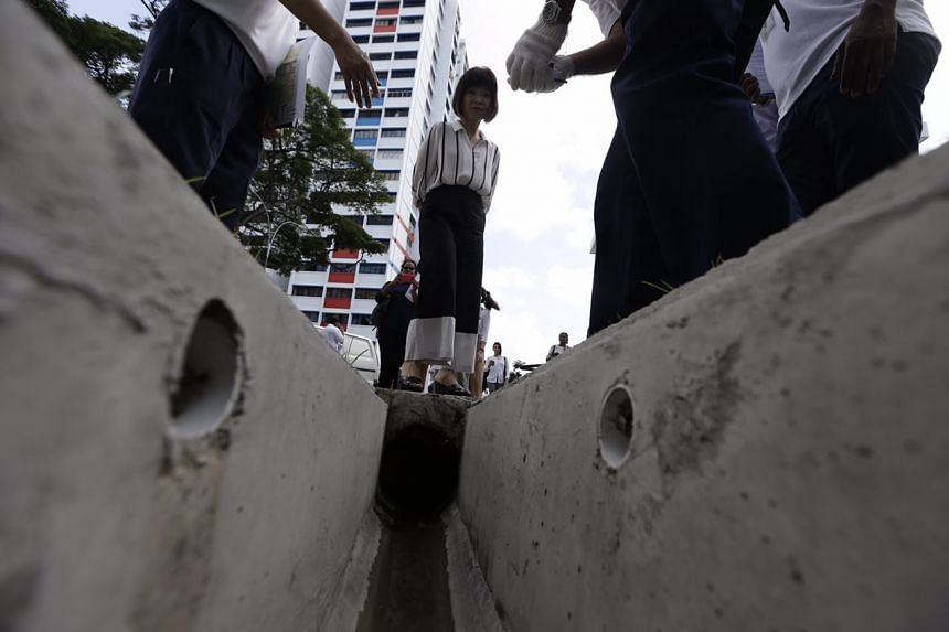 Dr Amy Khor watching as NEA officers treat the drains with chemical at Paya Lebar Way on Aug 31, 2016.