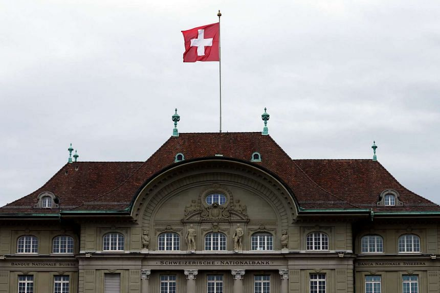A Swiss national flag flutters in the wind atop the Swiss National Bank SNB headquarters in Bern, Switzerland on April 16, 2015.