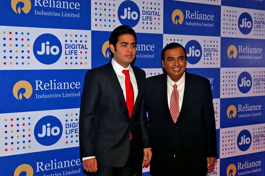 Mukesh Ambani (right), chairman of Reliance Industries Ltd, poses with his son Akash before addressing the company's annual general meeting in Mumbai, India on Sept 1, 2016.