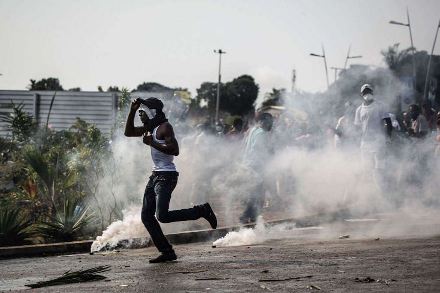 A protester runs amid tear gas canisters during confrontations with the police in Libreville on Aug 31, 2016.