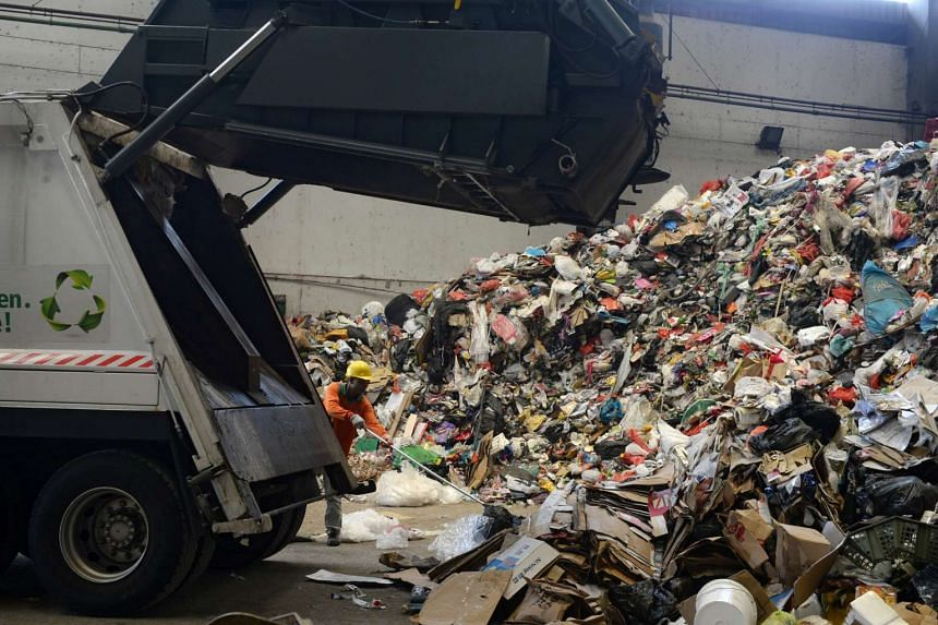 A rubbish truck dumps unsorted waste at the SembWaste Material Recovery Facility on March 21, 2016.