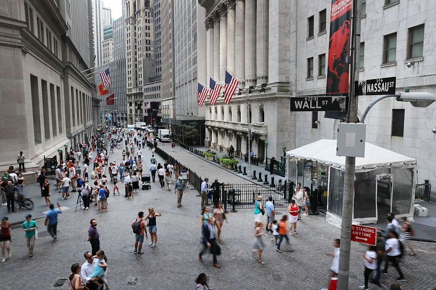 People walk outside of the New York Stock Exchange (NYSE) in New York City. Stocks ended lower on Wall Street on Wednesday (Aug 31), as energy shares tracked oil prices lower.