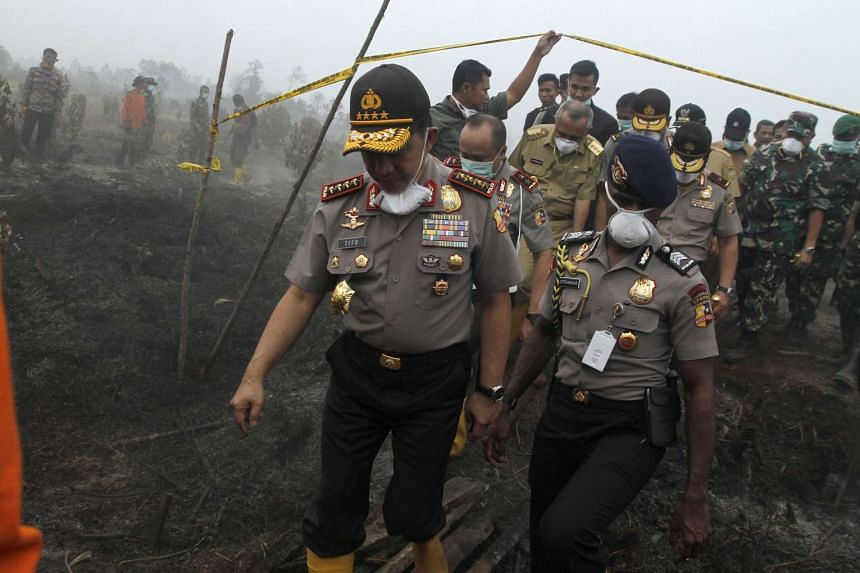 Indonesian Police Chief General Tito Karnavian (left) and staff examine land and forest fires.