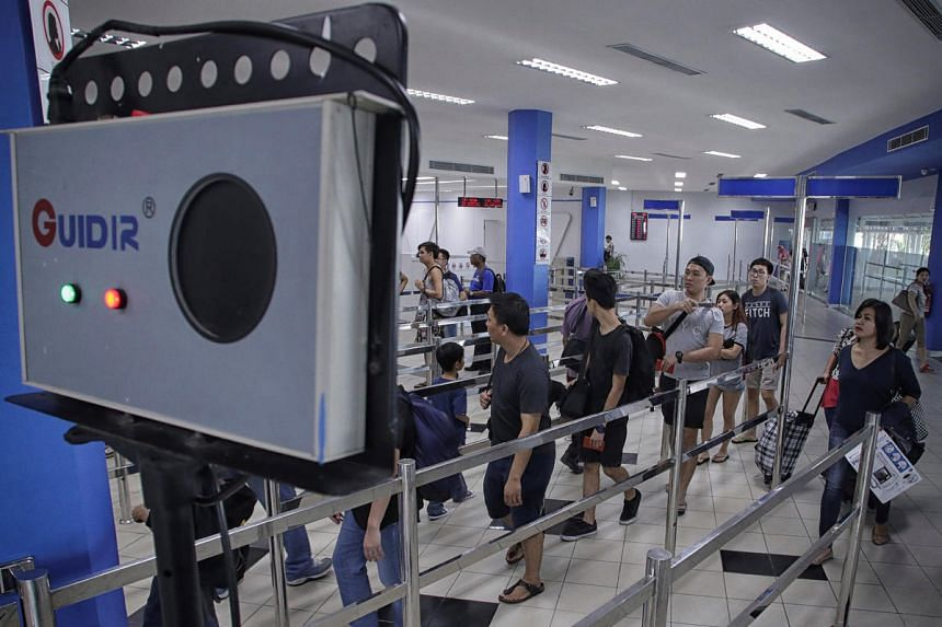 Passengers from a ferry from Singapore pass by an infrared scanner before passport control at the international ferry terminal in Batam, Riau Islands, Indonesia on Aug 31, 2016.