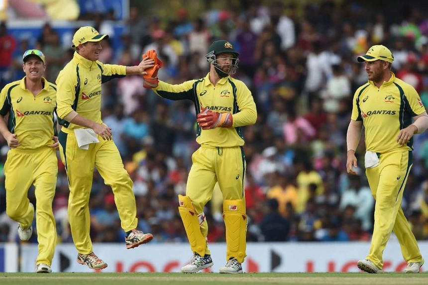 Australian wicketkeeper Mathew Wade (second right) celebrates with teammates after dismissing Angelo Perera.