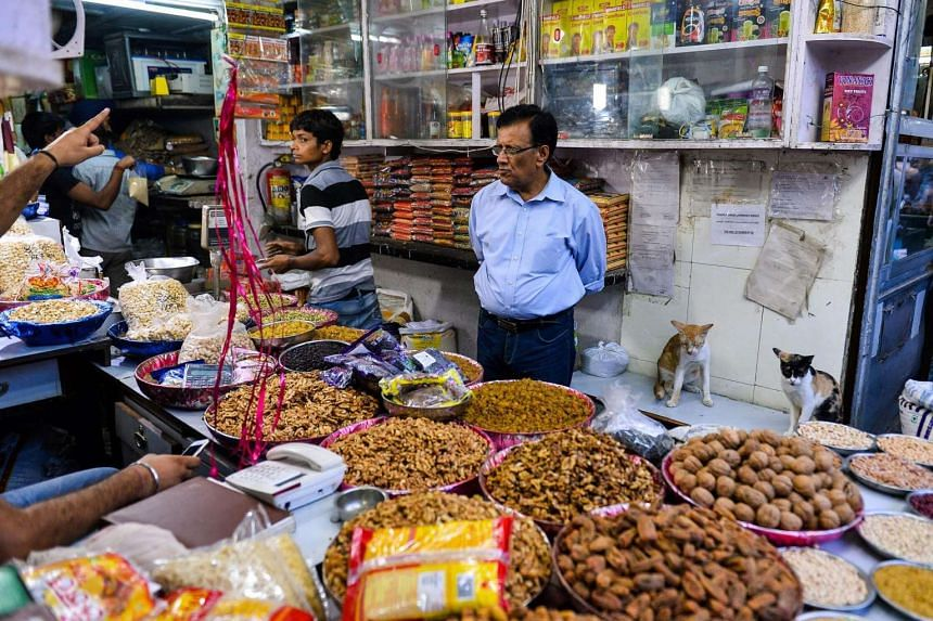 In this photograph taken on Aug 2, 2016, an Indian customer looks on as he peruses goods in a shop in the old quarters of New Delhi.