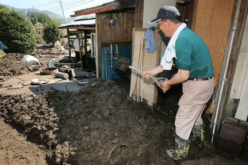 A resident removes mud around a building after Typhoon Lionrock made landfall in Iwaizumi, Iwate prefecture on Sept 1, 2016.