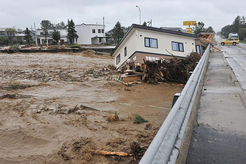 A house being swept down a river in the town of Shimizu in Hokkaido prefecture yesterday after Typhoon Lionrock struck overnight.