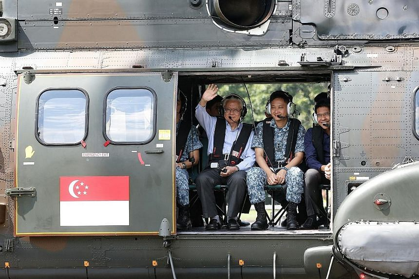 President Tan waving to the media during a ride in the Super Puma during his visit to the RSAF's Sembawang Air Base yesterday.