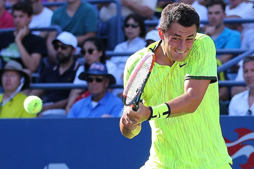 Bernard Tomic of Australia (above) returning a shot to Damir Dzumhur of Bosnia during their first-round match. Tomic was apparently taunted by a spectator and he responded with a foul-mouthed remark.