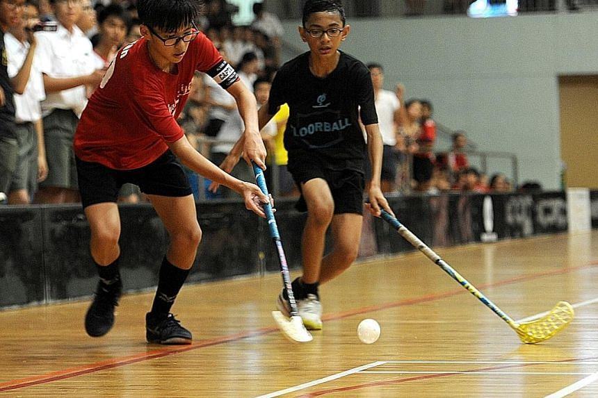Catholic High School (red) and Northbrooks Secondary School players in action during the Schools National C Division floorball final at Yishun Sports Hall. Both teams were first-time finalists, with CHS winning 3-2.