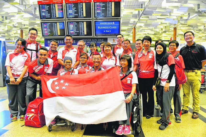 Para-athletes (front row, from second left) Suhairi Suhaini, Norsilawati Sa'at, Muhammad Diroy Noordin, para-sailors Jovin Tan, Yap Qian Yin and para-archer Nur Syahidah Alim (behind Tan) were in buoyant mood last night before flying to Rio de Janeir