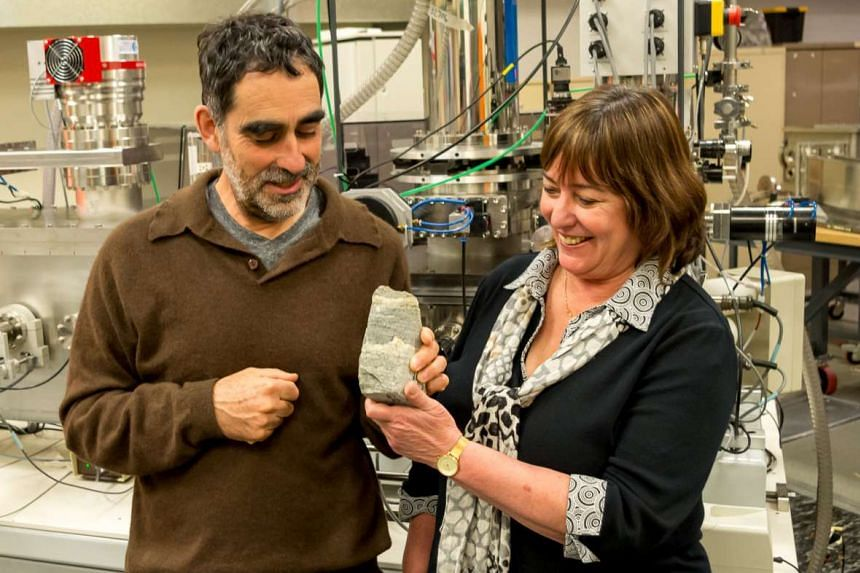 Nutman (left) of the University of Woollongong and Vickie Bennet of the Australian National University hold a 3.7 billion-year-old fossil specimen found in Greenland.