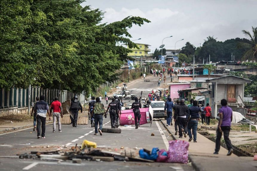 Gabonese police forces are seen clearing barricades in the streets adjacent to the National Assembly in Libreville on Sept 1, 2016.