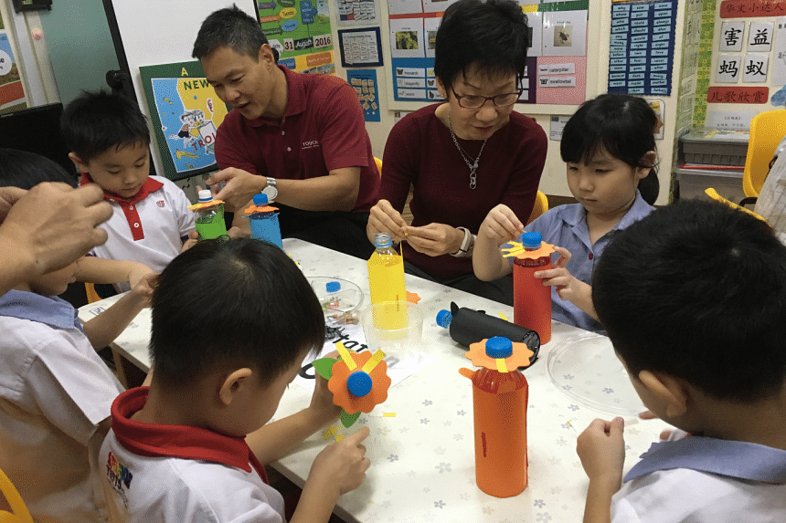 Ms Grace Fu, Minister for Culture, Community and Youth, helping the students at PCF Sparkletots Admiralty Childcare, make a piggy bank.