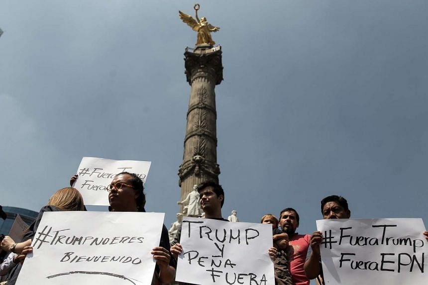 People protest against Donald Trump's visit in Mexico City on Aug 31, 2016.