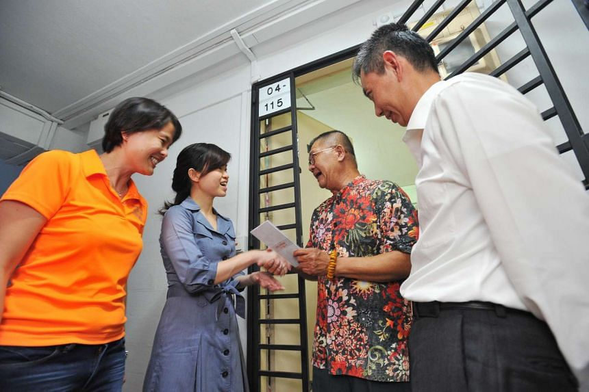 MP Tin Pei Ling (second from left) and Income CEO Ken Ng (extreme right) giving out the cards to eligible residents in four rental blocks along Pipit Road in Macpherson on Aug 31, 2016.
