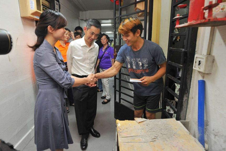 MP Tin Pei Ling (extreme left) and Income CEO Ken Ng (centre) giving out the cards to eligible residents in four rental blocks along Pipit Road in Macpherson on Aug 31, 2016.