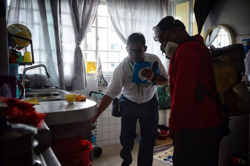 An NEA officer and a pest control worker inspect and spray insecticide at a household kitchen in Block 404, Bedok North Avenue 2, on Sept 1, 2016.