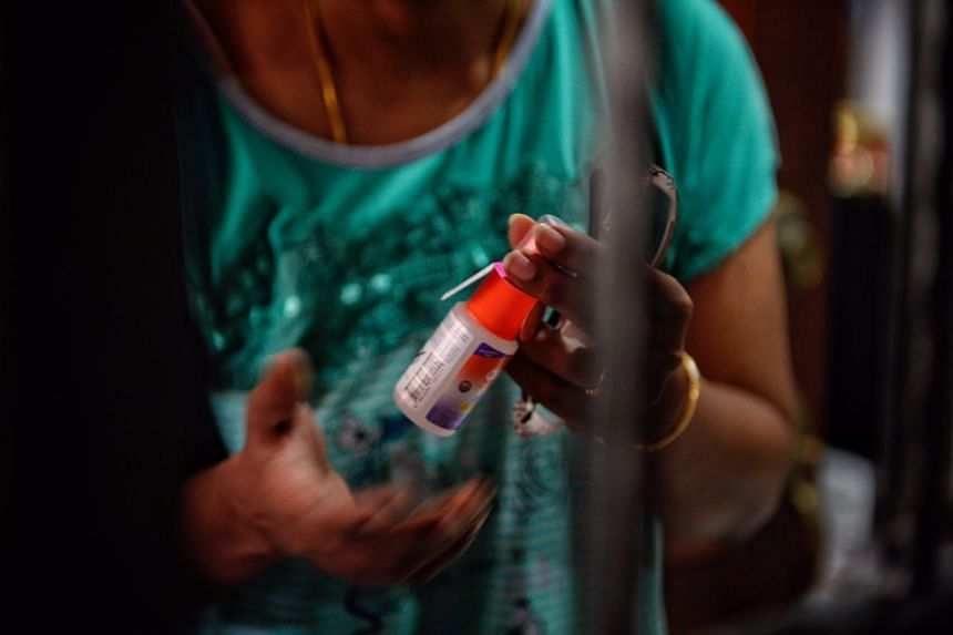 A Block 404 resident holds on to a bottle of repellent given to her by a town council member on Sept 1, 2016.