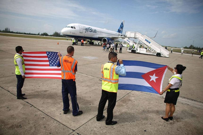 Ground crew hold US and Cuban flags as the JetBlue aeroplane arrives in Cuba.
