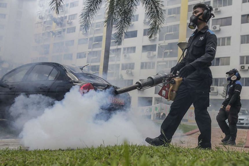 Pest exterminators fumigate a carpark in front of a block of flats in Aljunied on Aug 31, 2016.