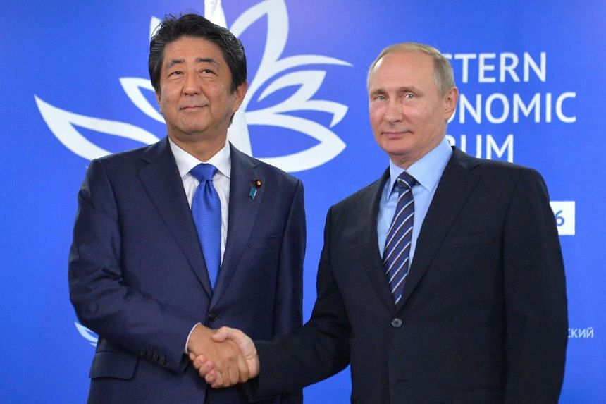 Russian President Vladimir Putin (right) shakes hands with Japanese Prime Minister Shinzo Abe during a meeting on the sidelines of the Eastern Economic Forum in Vladivostok on Sept 2, 2016.