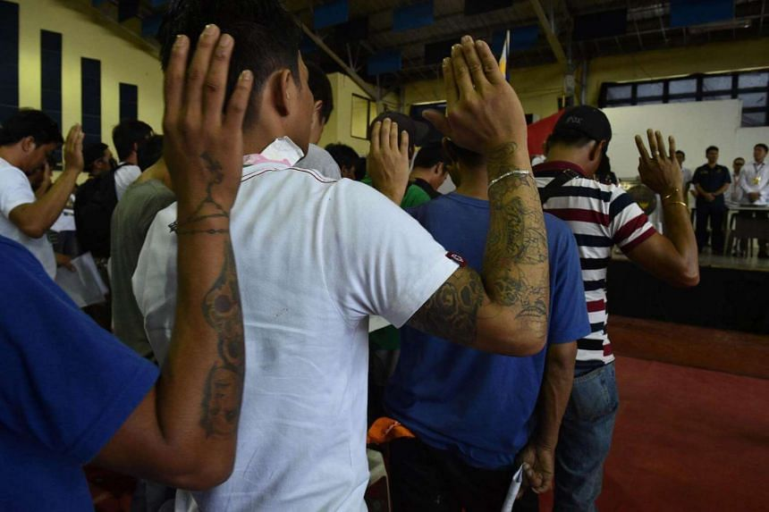 Drug users and dealers taking oath after they voluntarily surrendered to local authorities in Tanauan town, Batangas province, south of Manila on July 18, 2016.