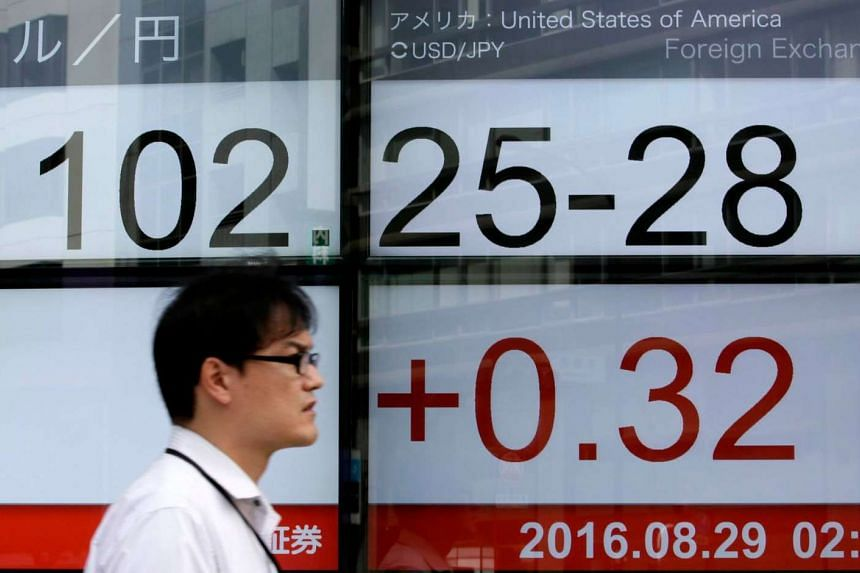 A man walks past a display showing the exchange rate between the Japanese yen and US dollar during an afternoon trading session in Tokyo, Japan on Aug 29.