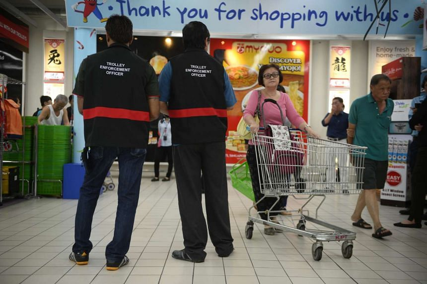 Trolley enforcement officers giving out fliers urging customers not to remove trolleys at NTUC FairPrice Xtra in Jurong Point.