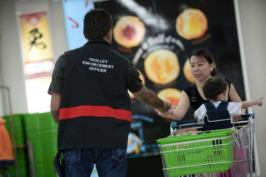 A trolley enforcement officer giving out fliers urging customers not to remove trolleys at NTUC FairPrice Xtra in Jurong Point.